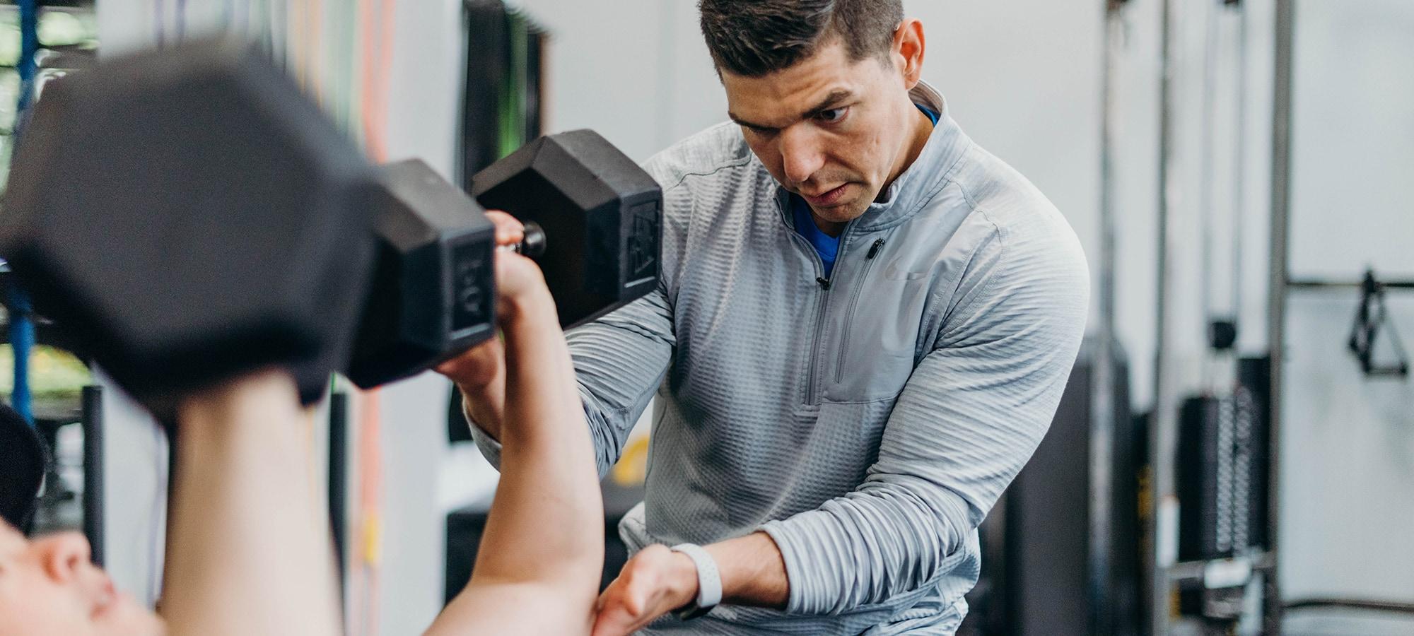 Sean Ferguson assisting man in bicep exercise